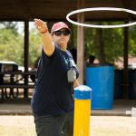A young woman throws a large ring during a game in the Carnival Games area during the ADA25 Celebrations.