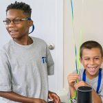 Two boy campers are smiling as they listen to an assistive technology device that is voice activated