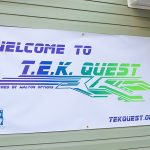 """The """"Welcome to TEK Quest"""" sign outside the Walton Office door. The text is in the TEK Quest blue and green."""