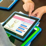 A instructor's hands are seen working with a tablet showing a program that a camper could use for math practice.