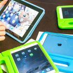 A close-up photo of an instructor's hands as she works with a tablet. There are extra tablets laying on the table in blue and green covers.