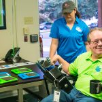 Instructor Sam takes a break and looks at the camera. He is wearing a green TEK Quest polo shirt and is sitting in his wheelchair. A female volunteer stands behind him looking at a table with tables in green and blue cases.