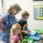 A camper and their caregiver works on a tablet with one of the instructors who is showing him how to operate the app.