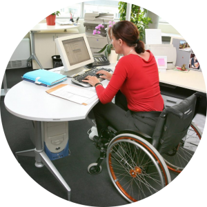 Woman with a disability is in her wheelchair at her desk working on a computer.