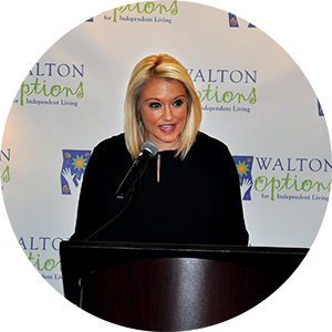 2017 MVP Community Awards Host Barclay Bishop speaks at the podium in front of the Walton Options backdrop during the luncheon.