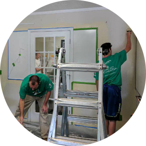 A candid shot of two men in green Comcast Cares t-shirts work in the North Augusta office painting walls.