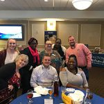 A quick group shot of members of the Walton Options team, our community partners and one of the Awards finalists. The group is at one of the tables, some of them are sitting while others are standing. They are all looking at the camera smiling.