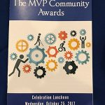 """A photo of the MVP Community Awards program sitting on a table. The program is dark blue with thite text reading """"Walton Options for Independent Living Presents The MVP Community Awards Celebration Luncheon, Wednesday, October 25, 2017, Legends Club, Augusta, GA. In the middle of the brochure is a graphic design with multi-colored cogs with a variety of stick figures next to the cogs."""