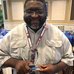 Recipient of the Walton Options' Dedicated Volunteer Award, Spencer, poses with his award for a quick photo following the luncheon. He is looking at the camera smiling.
