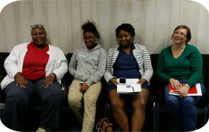 The I'm Sweet Peer Support group with four consumers sitting in a row looking at the camera smiling. The women are a variety of ages from young adult to older consumers.