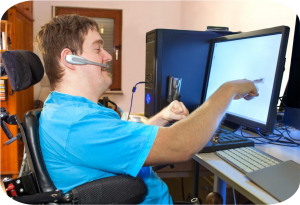 Man in a wheelchair with Cerebral Palsy works at an adapted desk using assistive technology to lead an independent life as a person with a disability.
