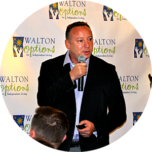 Guest Speaker of the 2017 MVP COmmunity Awards Luncehon - Jeff Eiseman stands in front of the Walton Options backdrop speaking during his presentation during the luncheon.