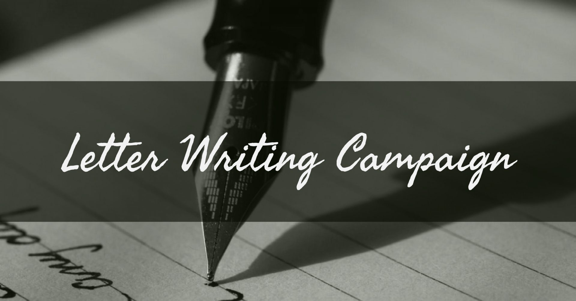 black and white photo of a close-up of an fountain pen writing on lined paper with a text box imposed over the center of the image. Text in the box reads: Letter Writing Campaign.