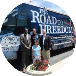 A group of four people, three gentleman and one lady, pose in front of the Road to Freedom Tour Bus during the ADA25 Celebration tour in May 2015