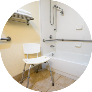 Assistive equipment in a bathroom including grab bars and a shower chair